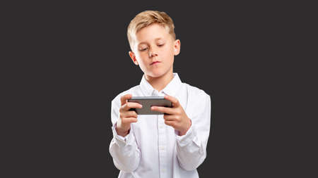 Mobile game addiction. Online entertainment. Confident boy playing on smartphone isolated on dark background. Stock Photo