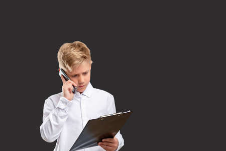 Children in business. Progressive generation. Smart boy working on project talking on phone isolated on gray.