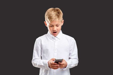 Online communication. Impressive news. Surprised boy reading message on phone isolated on dark background.