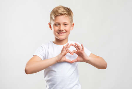 Love sign. Affection compassion. Friendly blond boy showing heart gesture isolated on neutral background.