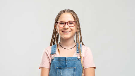 Smart kid portrait. Back to school. Happy girl in eyeglasses with braids smiling isolated on neutral background.