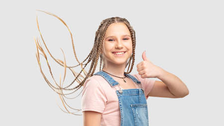 Satisfied kid portrait. Like gesture. Playful teen girl showing thumb up smiling isolated on white background.