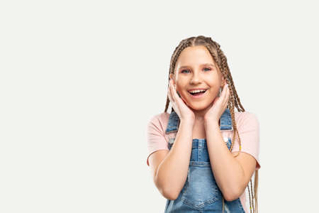 Amazed kid portrait. Great news. Astonished girl touching cheeks smiling isolated on white empty space.