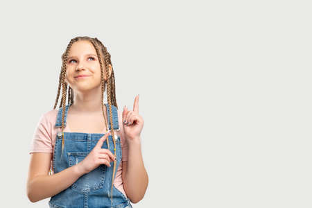 Happy child portrait. Commercial background. Satisfied girl isolated smiling pointing at neutral empty space.