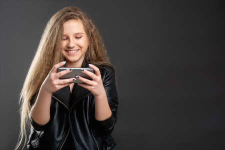 Online fun. Mobile app. Excited teen girl enjoying watching comedy show on phone isolated dark copy space. Stock Photo