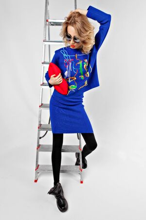 Young stylish blonde girl with red lips in sunglasses is dressed in a blue suit and boots is standing on a white background and is leaning on a ladder Stock Photo