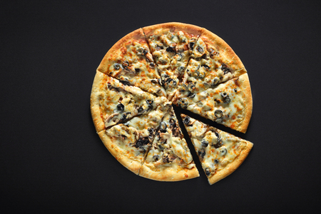 Pizza with ham and champignons olives on a black stone background