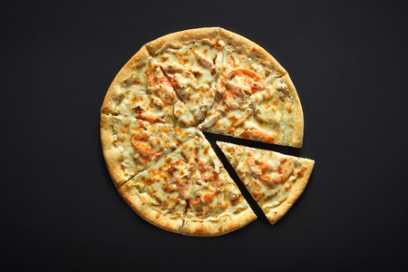Pizza with chicken cheese and tomato on a black stone background