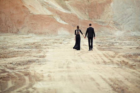 The bride and groom dressed in black are leaving
