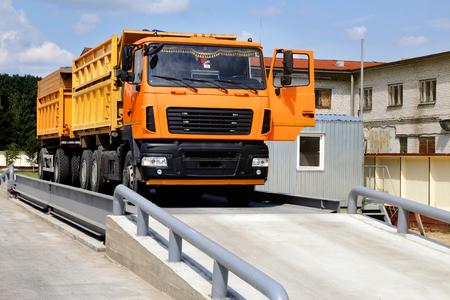 Il camion arancione con il grano viene pesato sulla bilancia nell'area di stoccaggio del grano. Bilance per autocarri