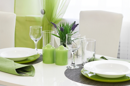festive table setting in green and white with candles on the table Stok Fotoğraf
