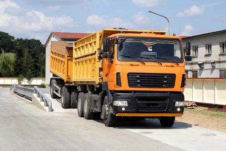 Il camion arancione con il grano viene pesato sulla bilancia nell'area di stoccaggio del grano. Bilance per camion