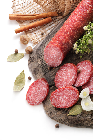 still-life with smoked sausage, salami bay leaf and onion on a wooden aged texture on a white background Reklamní fotografie