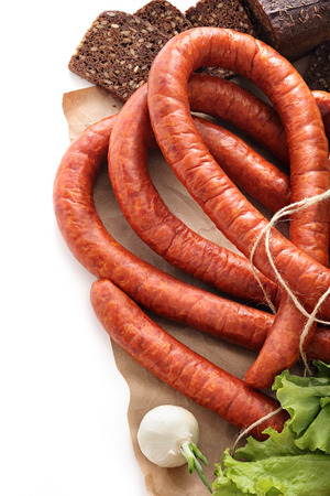 Still life, smoked sausage, onion black bread and lettuce leaves on kraft paper on a white background Stok Fotoğraf