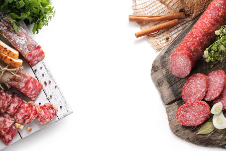 still-life with smoked sausage, salami bay leaf and onion on a wooden aged texture on a white background Stok Fotoğraf