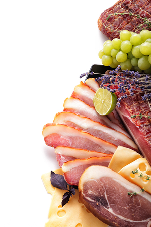 Assortment of meat products, including ham, bacon on white background, cheese, grapes, isolated, top view