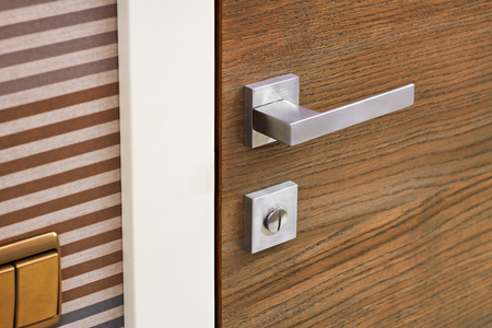 Modern metal door handle on wooden door texture