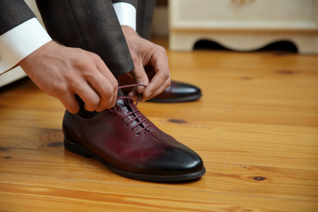 closed lacing, a man laces up his shoes on a wooden floor