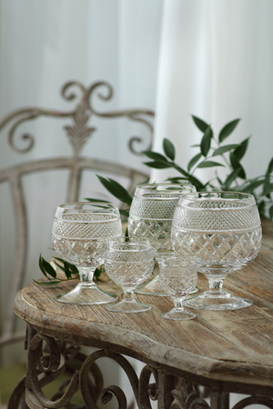 vintage glass goblets on a wrought-iron table with a wooden worktop