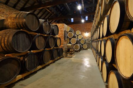 Rows of alcoholic barrels are kept in stock. Distillery. Cognac, whiskey, wine, brandy. Alcohol in barrels, alcohol storage