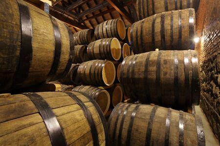 Filas de barriles de alcohol en stock. Destilería. Coñac, whisky, vino, brandy. Alcohol en barriles
