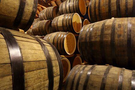 Rows of alcohol barrels in stock. Distillery. Cognac, whiskey, wine, brandy. Alcohol in barrels Stok Fotoğraf