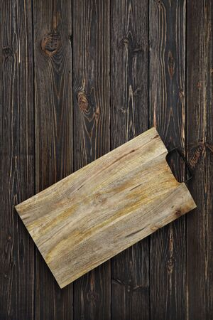 Wooden cutting board on a dark wooden background from boards.