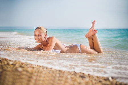 Beautiful young woman on the sand on the seashore photo