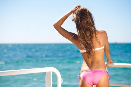 back woman on the seashore in bikini photo