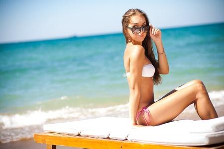 swim mask: beautiful woman on a tropical beach on a chaise lounge
