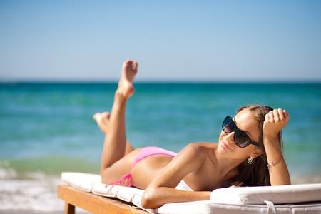 strandstoel: mooie vrouw op een tropisch strand op een chaise lounge Stockfoto
