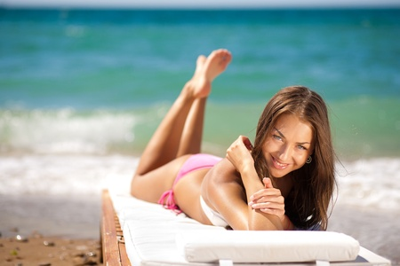 beautiful woman on a tropical beach on a chaise lounge photo