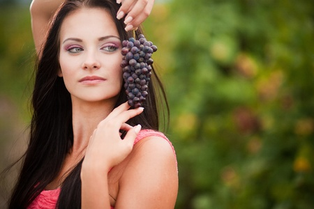 Portrait of young beautiful woman in grapes photo