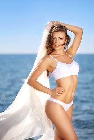 Beautiful young woman smiling in bikini on the sea photo