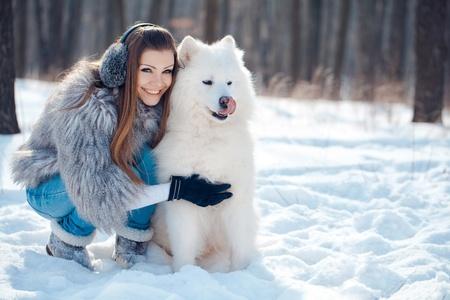 ropa invierno: Mujer feliz con el perro samoyedo en el bosque de invierno Foto de archivo