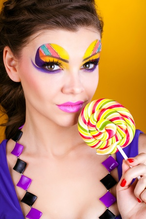 portrait of a glamourous beautiful woman holding lollipop photo