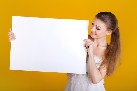 Smiling woman with white blank on yellow background