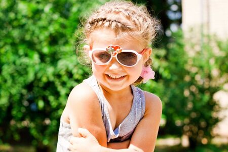 Beautiful Happy Little Girl outdoor in sunglasses photo