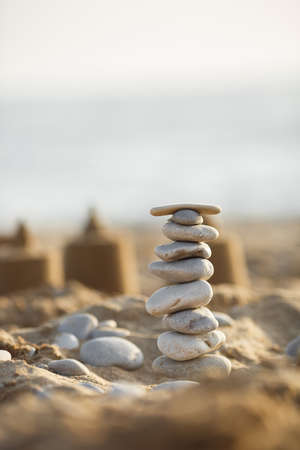 Meeressteine ragen auf Sand auf. Sommer und Sonnenuntergang auf Seehintergrund. Entspannung und Meditation am Strand. Foto in hoher Qualität Standard-Bild