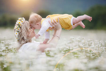happy woman with little baby boy in camomilles. blooming white field. family in flowers. mother and son Standard-Bild