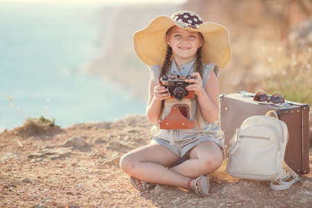 child girl traveler. trip alone. girl walking with camera and suitcase on nature by sea. travel, vacation, holidays Banco de Imagens