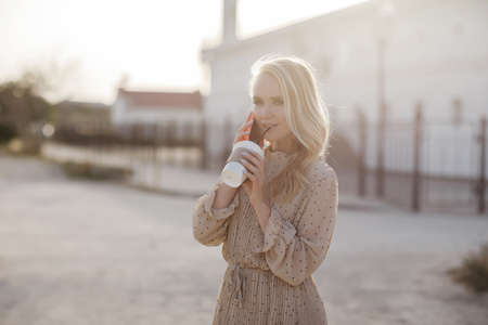 Young pretty woman with coffee speaking phone outdoor