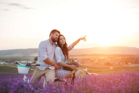 happy couple in laveder field. man and woman in sunset light in blooming lavender Archivio Fotografico