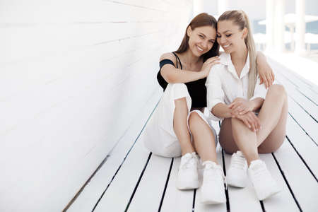 Two friends women sitting outdoor near white wall Archivio Fotografico