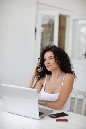 Young woman working at home with laptop shopping and surfing internet 스톡 콘텐츠