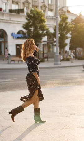 happy young woman walking on city street in sunset warm light. Smiling emotional girl outdoors in summer