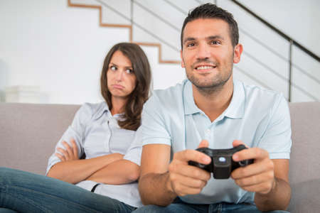 Bored girlfriend and her man playing video games Stock fotó