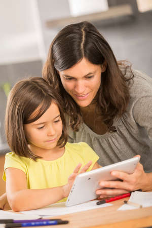 mother and daughter doing homework with a tablet Stock Photo