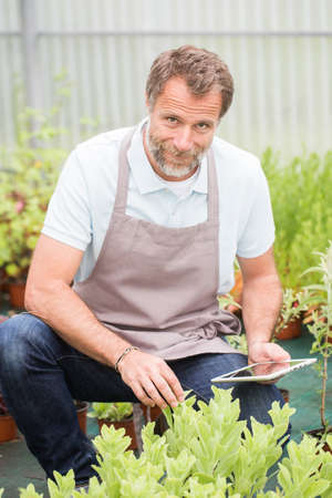 Attractive senior man working in a green house and using a tablet Stock Photo