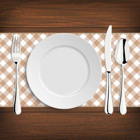 Plaat met lepel, mes en vork op een houten tafel.